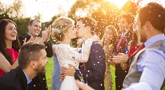 Newly married couple kissing under confetti